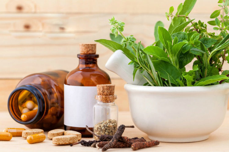 capsule, tablets, dried seeds on bottle and on the table as well as a bowl of fresh herbal leaves, useless supplements
